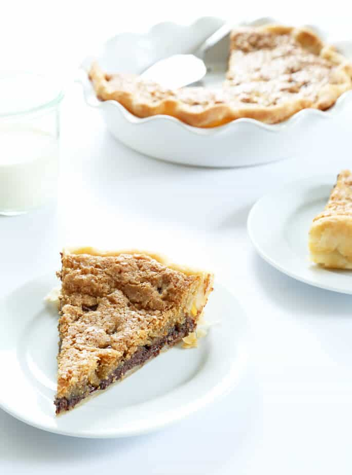 A slice of chocolate chip pie on a white plate