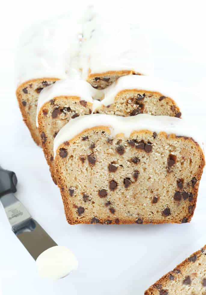 A few slices of glazed cannoli bread on a white surface