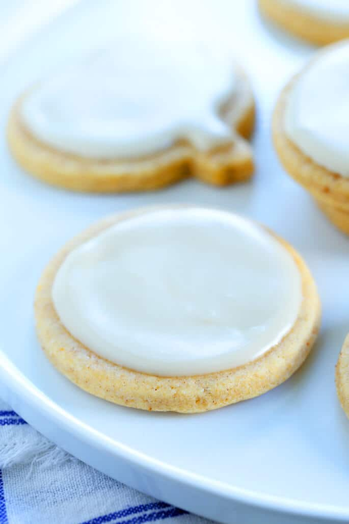 Close up of sugar cookie with vanilla glaze on a white plate