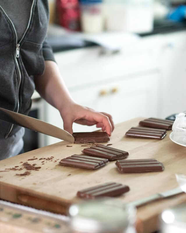 """A person cutting \""""kit Kat\"""" bars on a cutting board"""