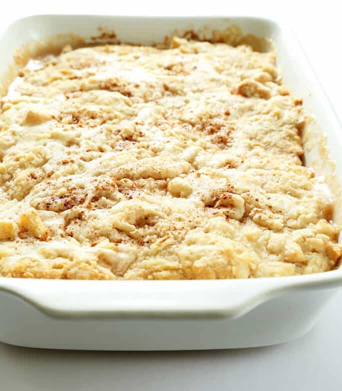 """A white dish with apple \""""dump\"""" cake"""