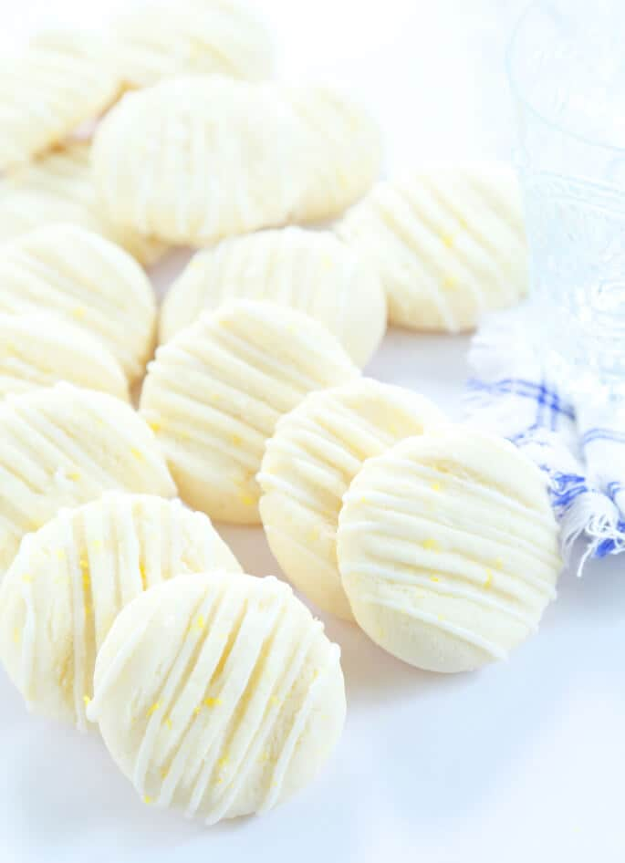 Lemon meltaway cookies on white surface with lemon zest on top