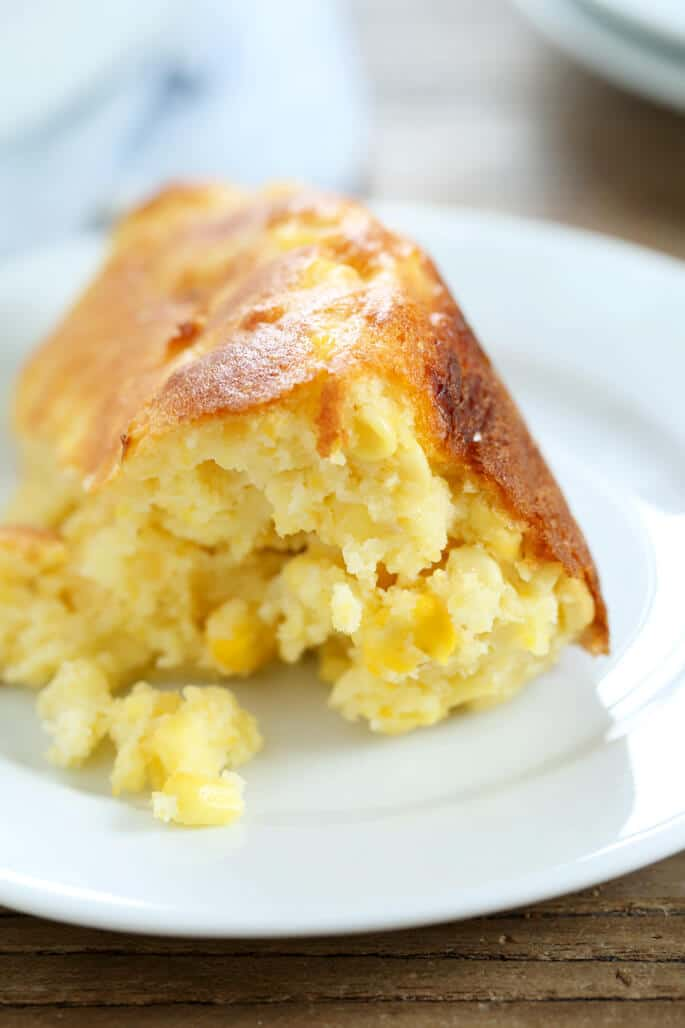 A close up of a serving of cornmeal spoonbread on a plate