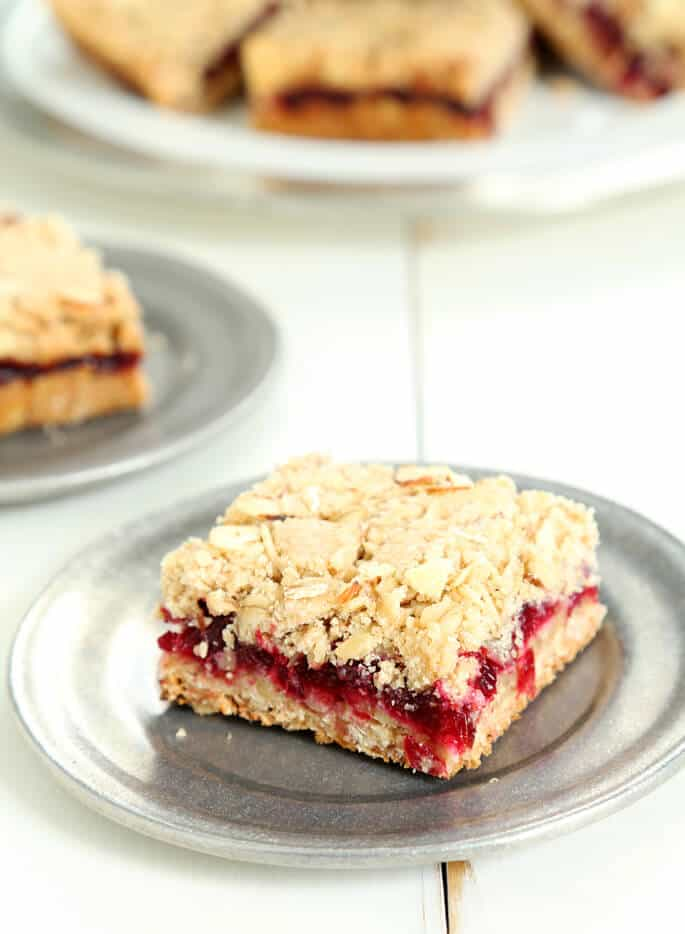 A close up of a cranberry jam bar on a sliver plate