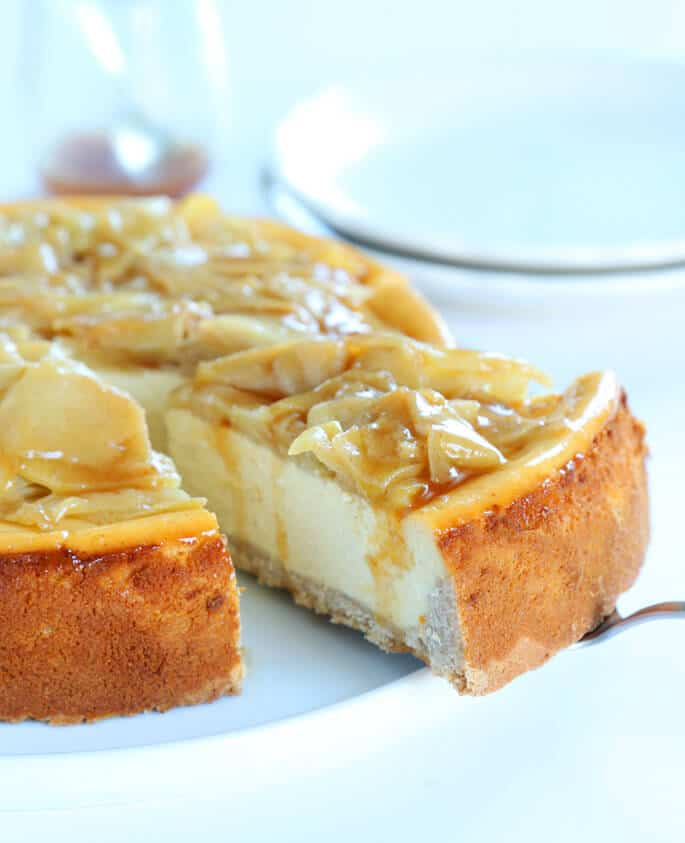 Apple cinnamon on cheesecake with slice being taken