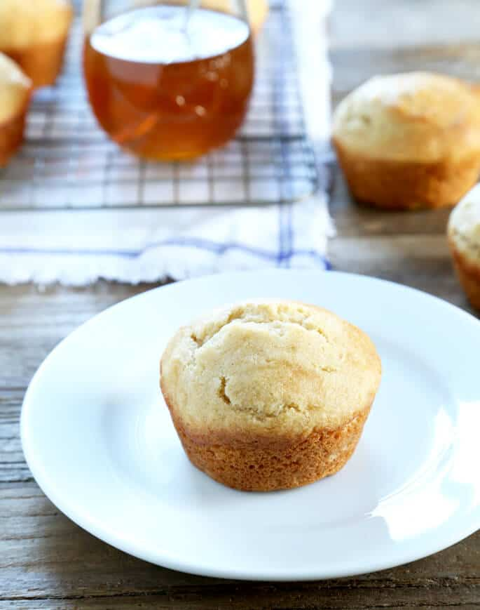A close up of a honey muffin on a white plate