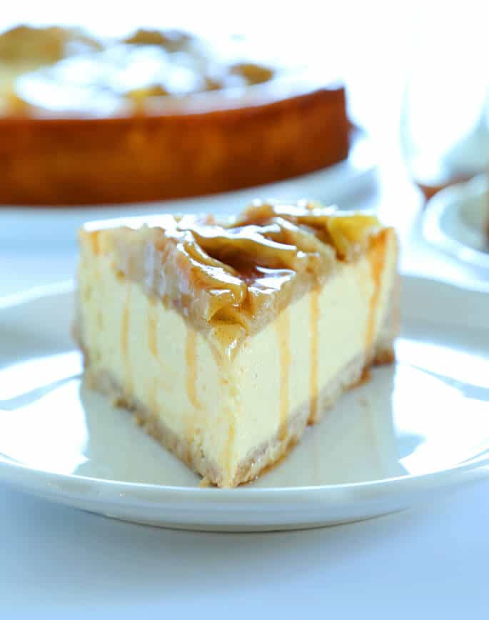 A close up of a slice of apple cinnamon cheesecake on a white plate