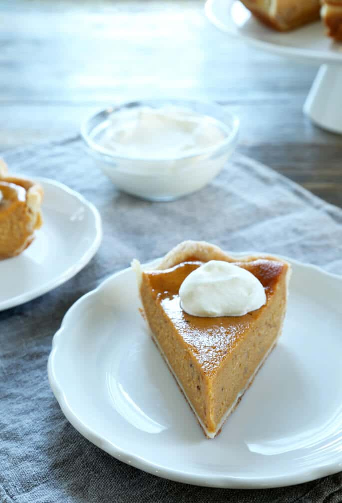 A slice of pumpkin pie with whip cream on a white plate