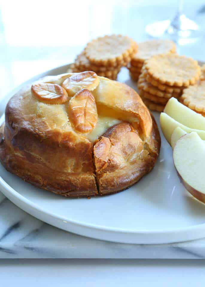 A plate with a close up of Brie en Croute, apple slices and crackers in back