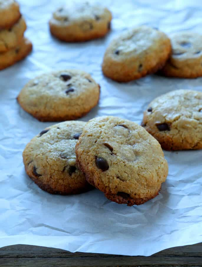 Chocolate chip cookies leaning against each other on a white surface