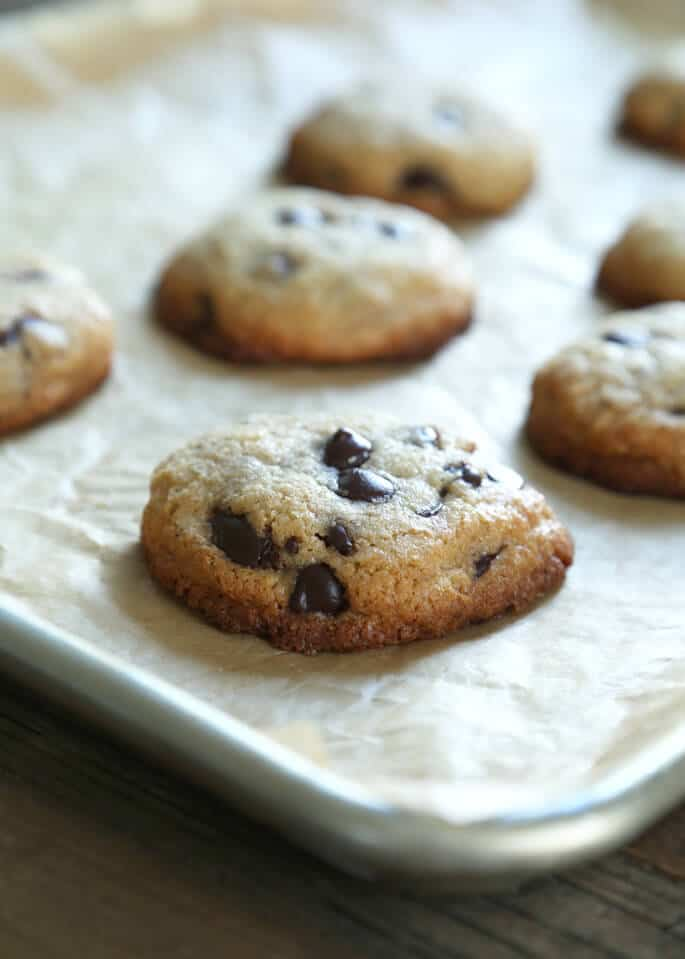 A close up of chocolate chip cookies on parchment paper
