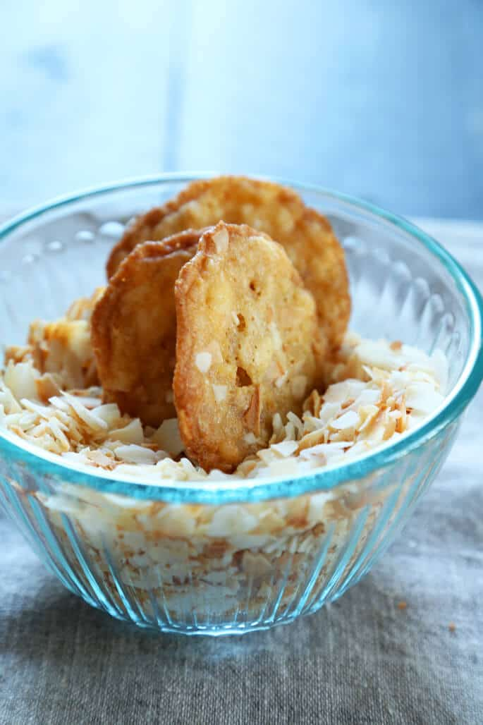 A bowl of with coconut chips and coconut cookies