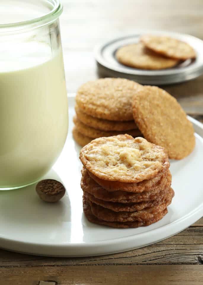 Stack of cookies on a plate with a jar of egg nog