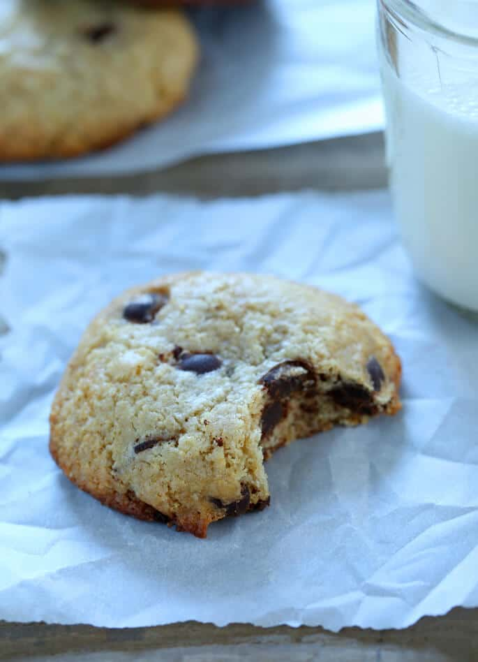 A close up of chocolate chip cookie with a bite taken out of it on a white surface