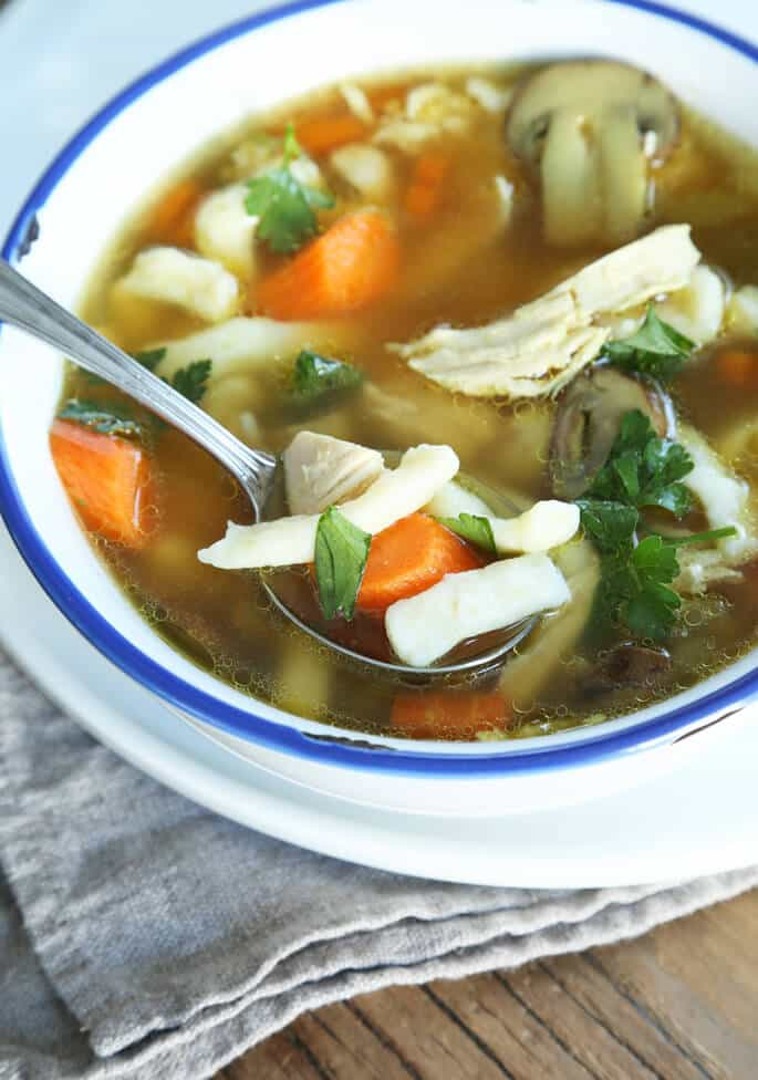 A bowl of chicken noodle soup with spoon