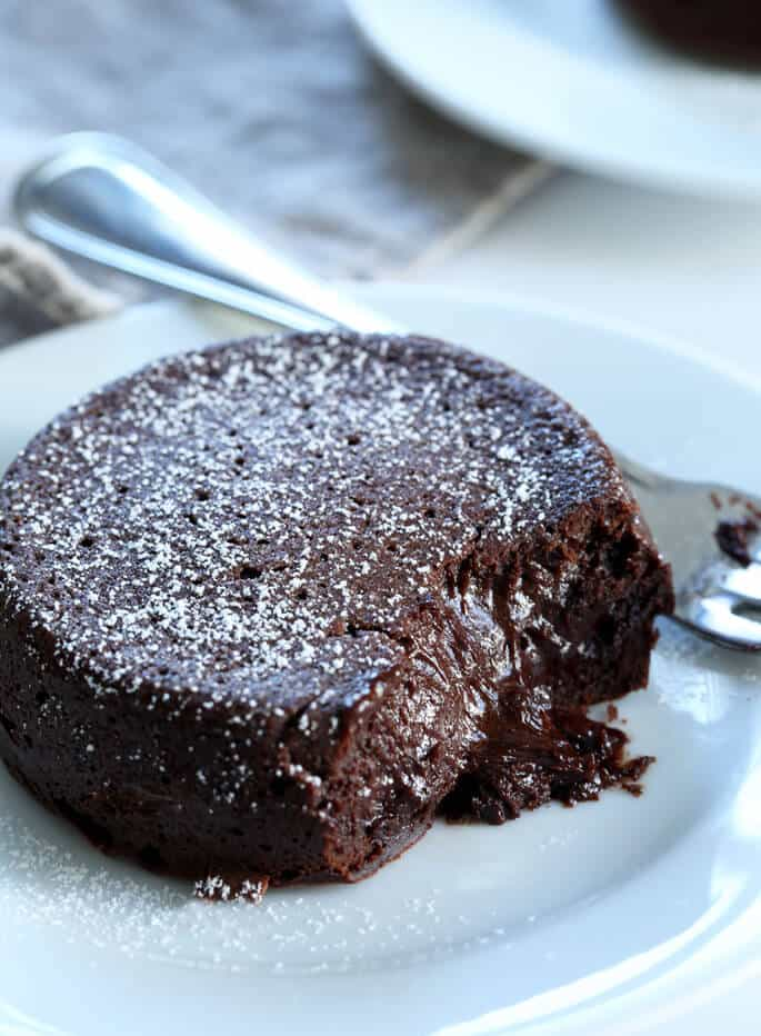 A close up of a chocolate lava cake on a white plate