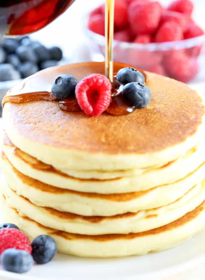 Close up of a stack of pancakces with syrup being poured over them