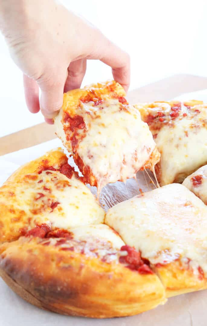 A close up of a person taking a slice of deep dish pizza