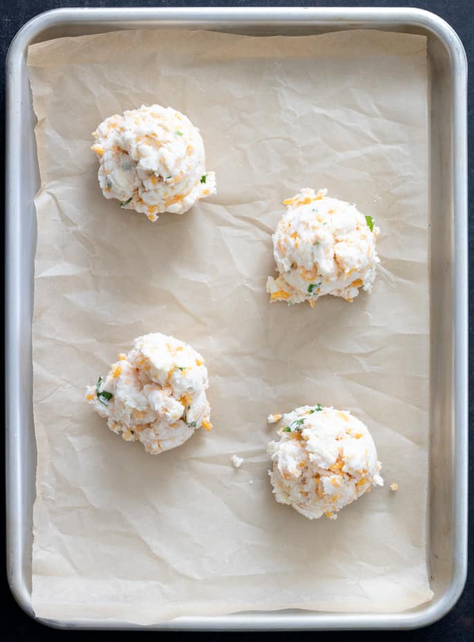 Raw mounds of gluten free cheddar bay biscuits, overhead image