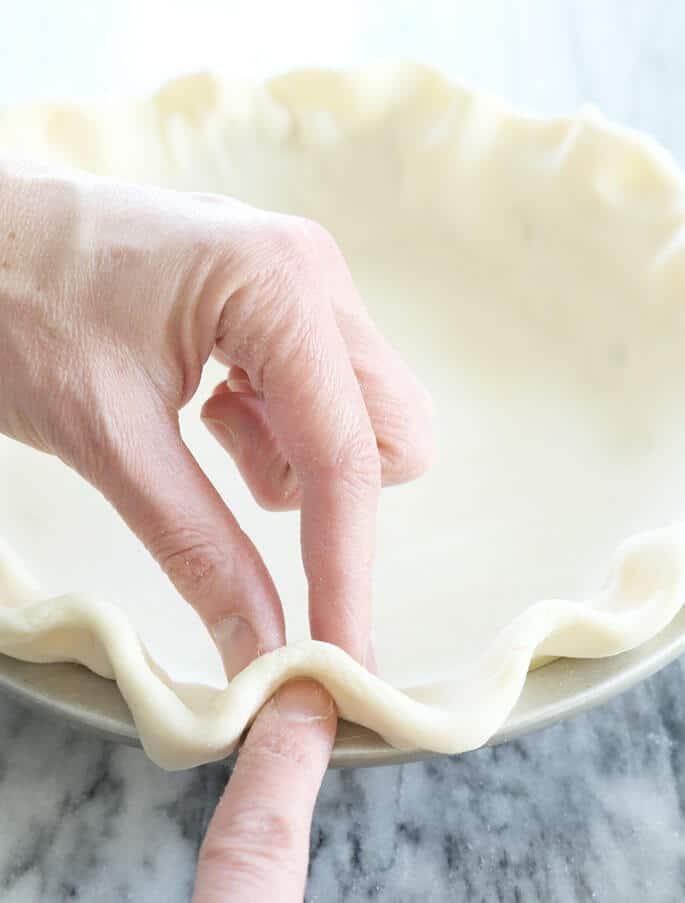 Hands crimping gluten free pie crust