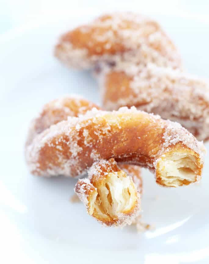 A close up of inside of cinnamon sugar biscuit donut twist on white plate