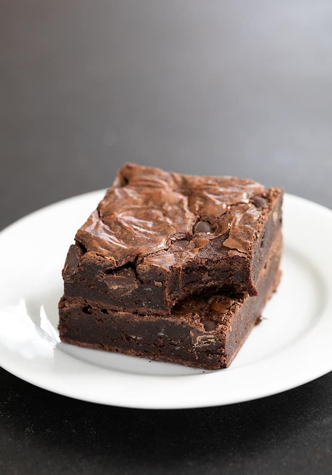 Two flourless brownies on a plate, in a stack