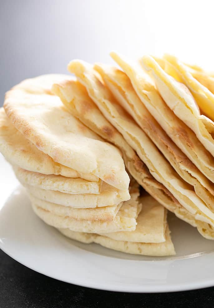 Stack of yeast free gluten free pita breads, sliced and ready to serve