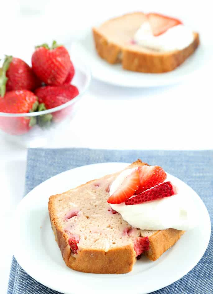 Strawberry bread with strawberries and whip cream on a white plate
