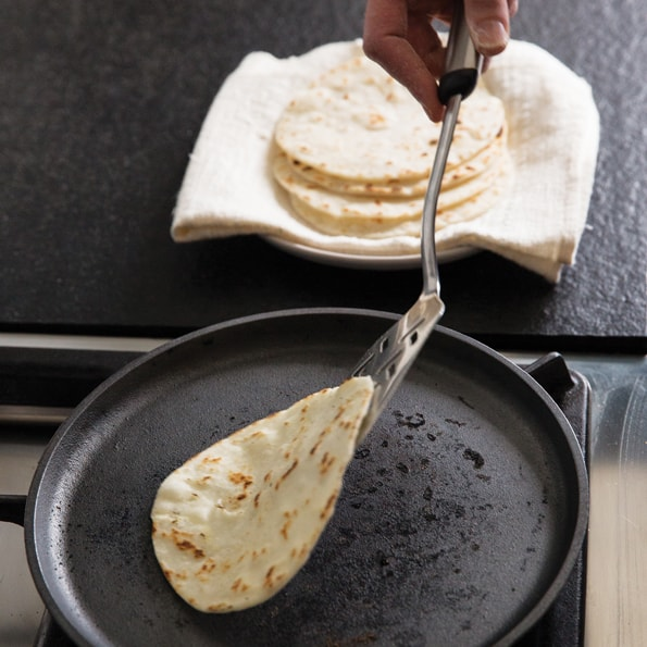 Flour tortilla being flipped with metal spatula on black pan