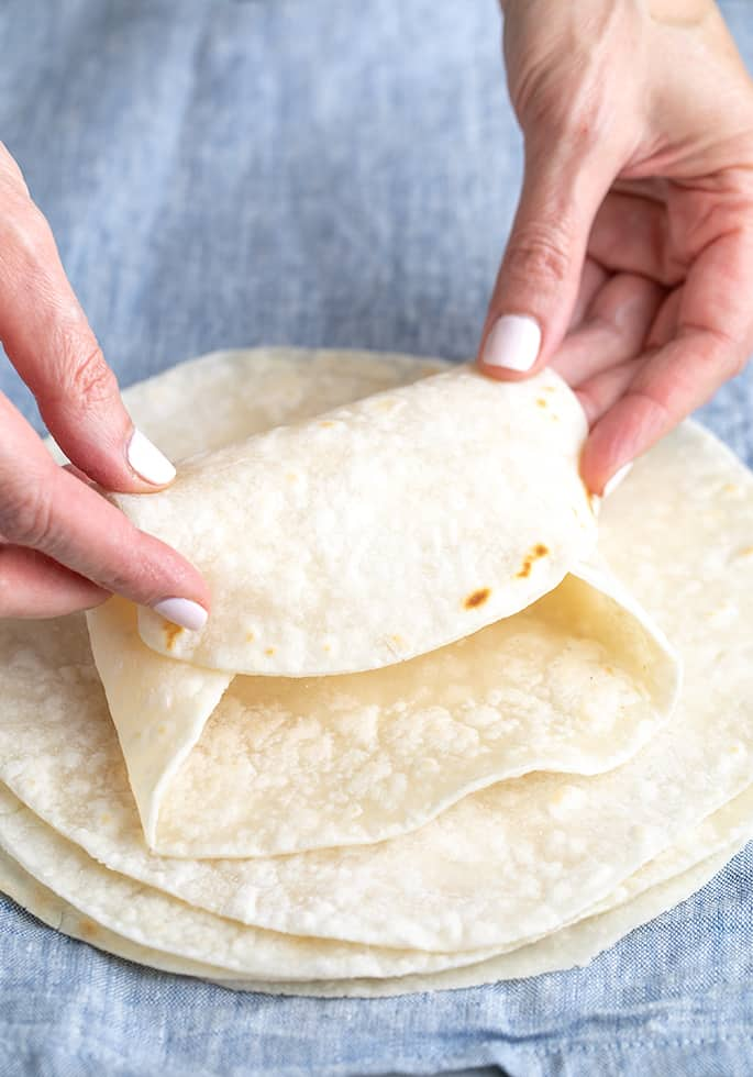 Hands folding top tortilla on a stack into a burrito shape, on blue cloth
