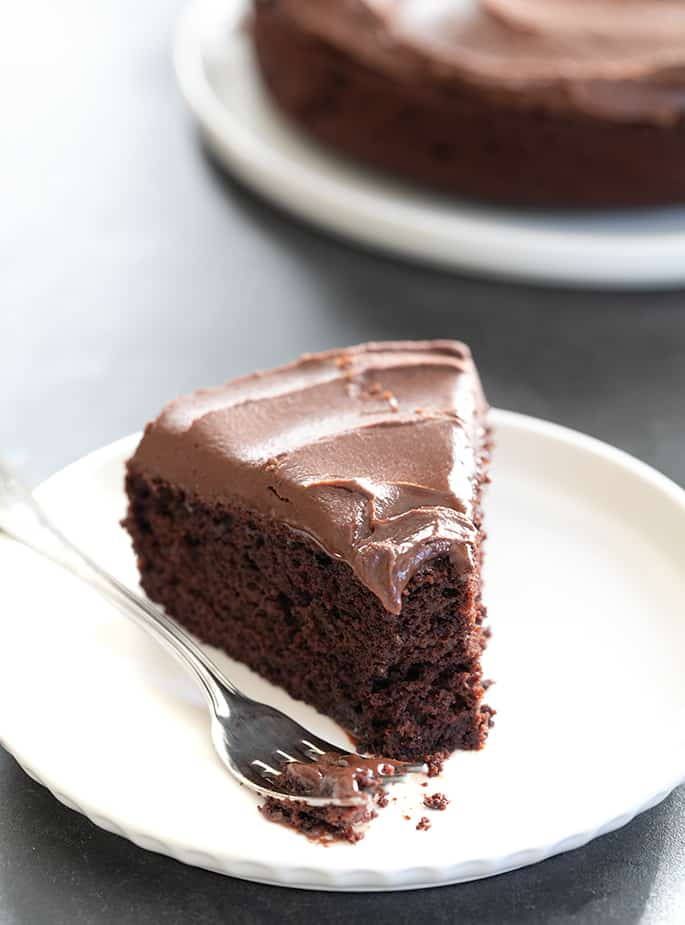 A piece of chocolate cake on a plate, with Ganache, and a bite taken.