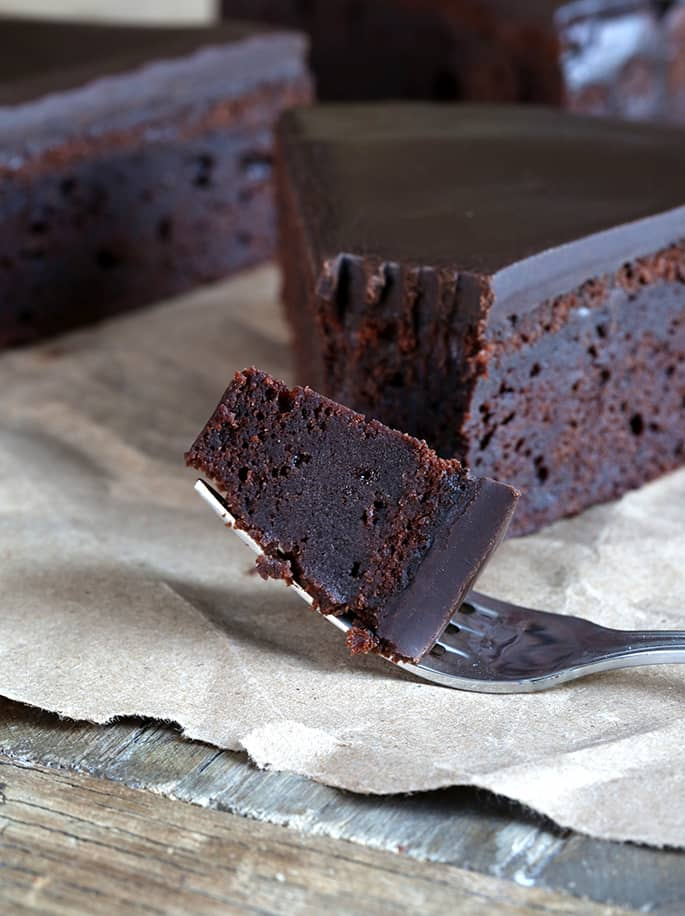 A forkful of chocolate cake with ganache topping