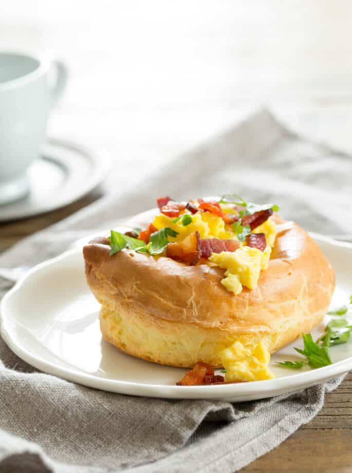 A white plate with a breakfast puff topped with eggs, bacon and herbs