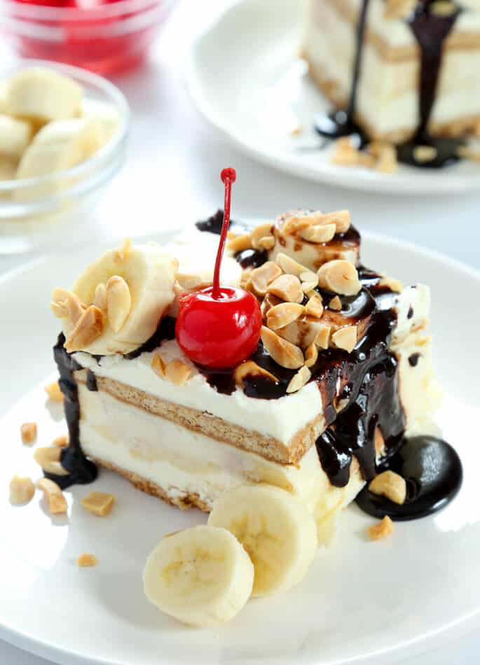 No Bake Banana Split Cake, made gluten free. A graham cracker crust, topped with fluffy cream cheese, bananas, crushed pineapple, vanilla pudding and whipped cream—and a cherry on top!