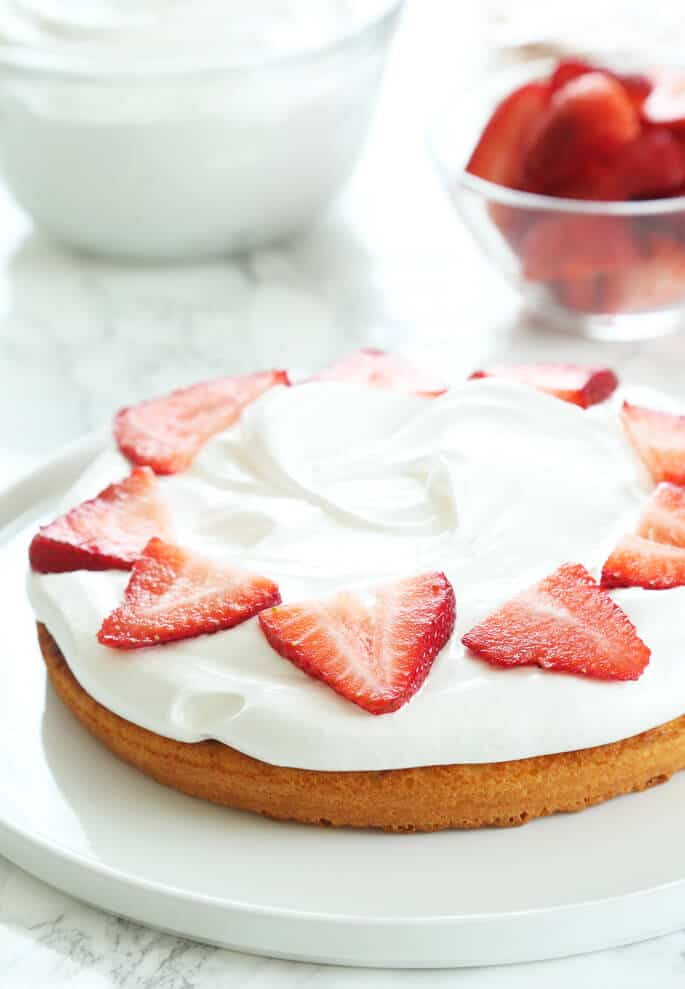 A sponge cake on a white cake with strawberries on top