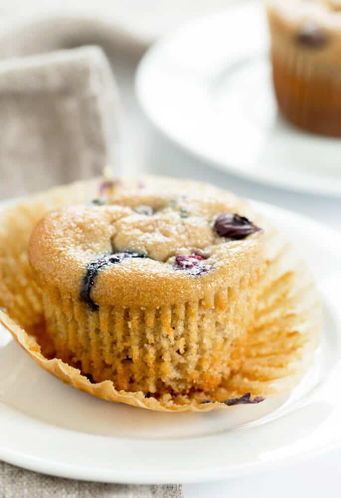 A close up of a muffin with blueberries on a white plate