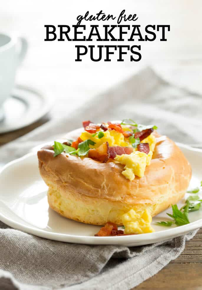 Close up of a breakfast puff on a white plate that has eggs, herbs and bacon bits on top