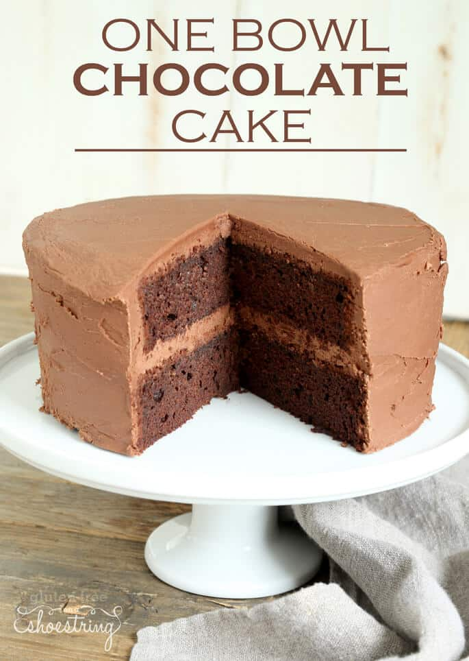 A chocolate cake on a cake plate with two slices removed