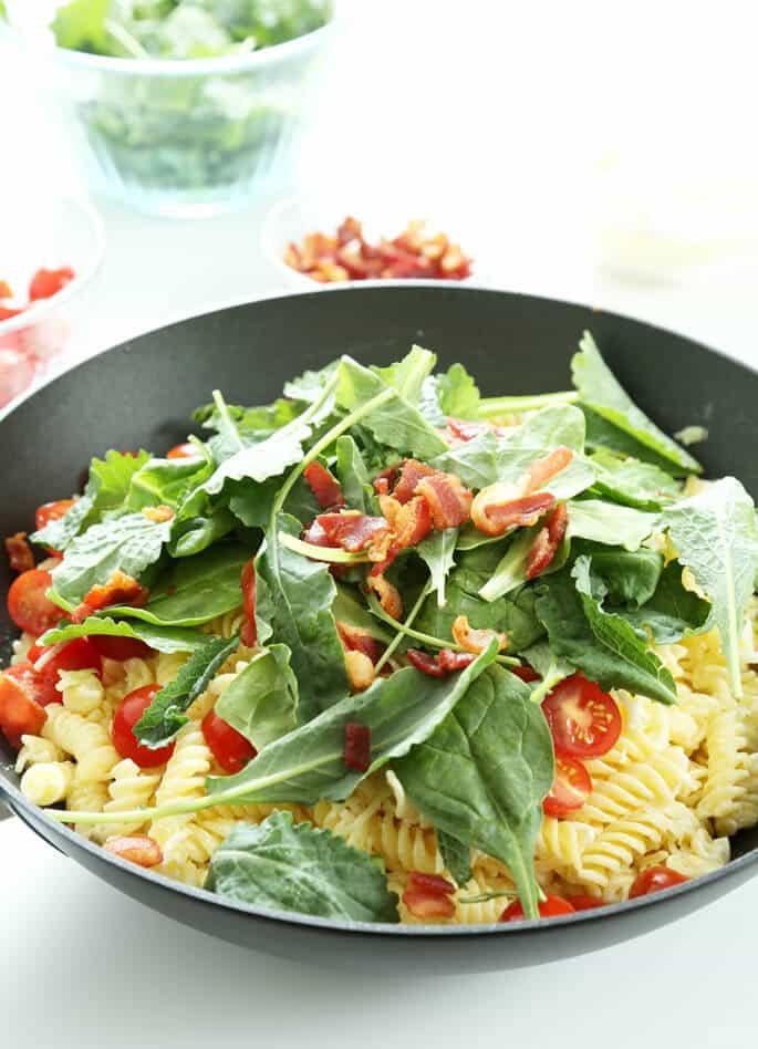 Arugula leaves on a bowl of BLT pasta