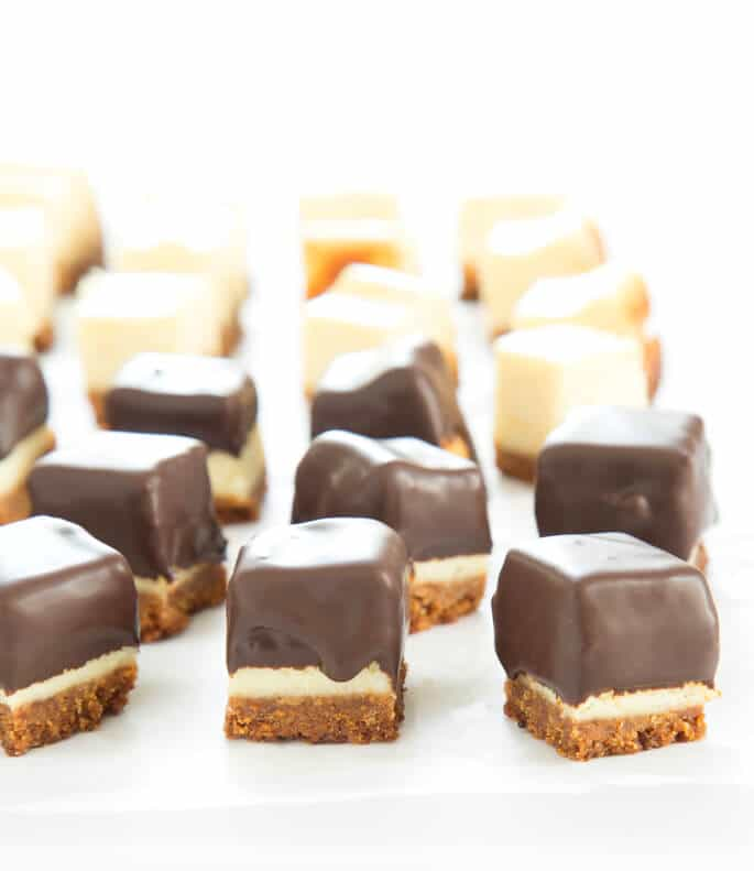 Squares of cheesecake half with chocolate coating and half without