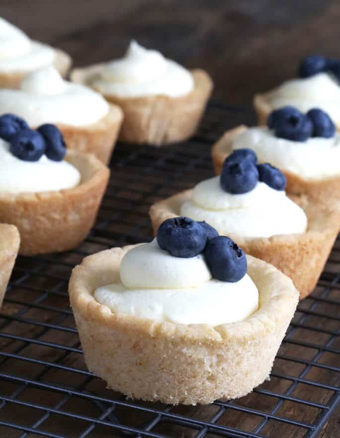 Gluten free sugar cookie cups filled with no-bake cheesecake filling—or your favorite berries and cream. Summer perfection!