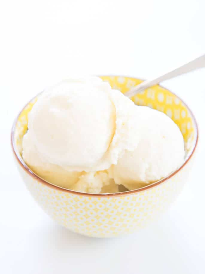 Yellow bowl with vanilla ice cream and spoon on white surface