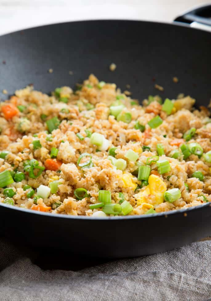 Close up of cauliflower fried rice in a black pan