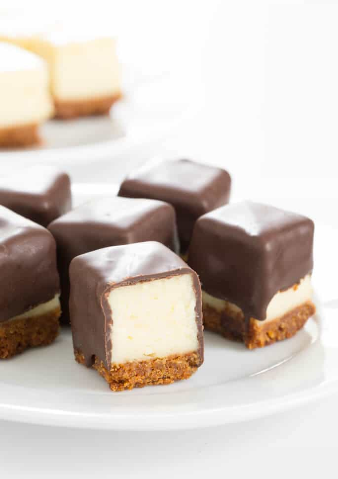 Cheesecake squares on a plate coated in chocolate, with one sliced open