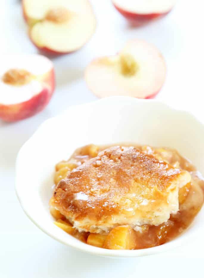 A close up of peach cobbler in a white dish