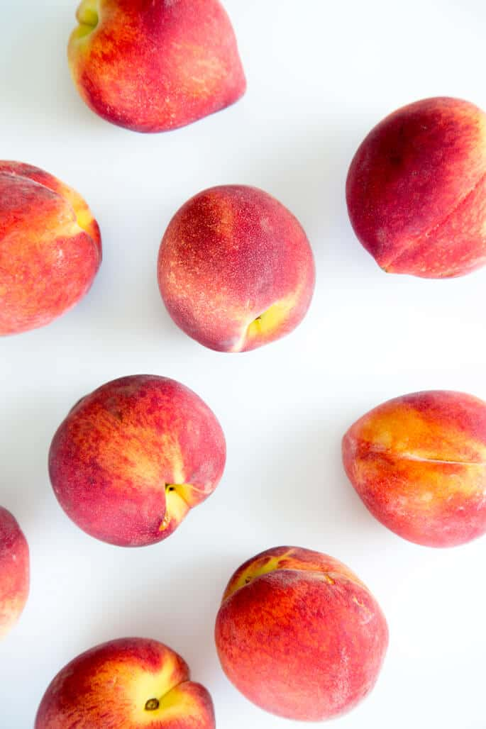 Overhead view of peaches on white surface