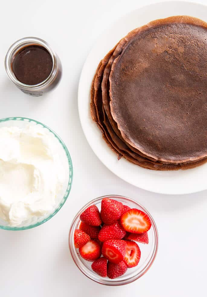 Overhead view of chocolate crepes and a bowl of whip cream, bowl of chocolate sauce and a bowl of strawberries