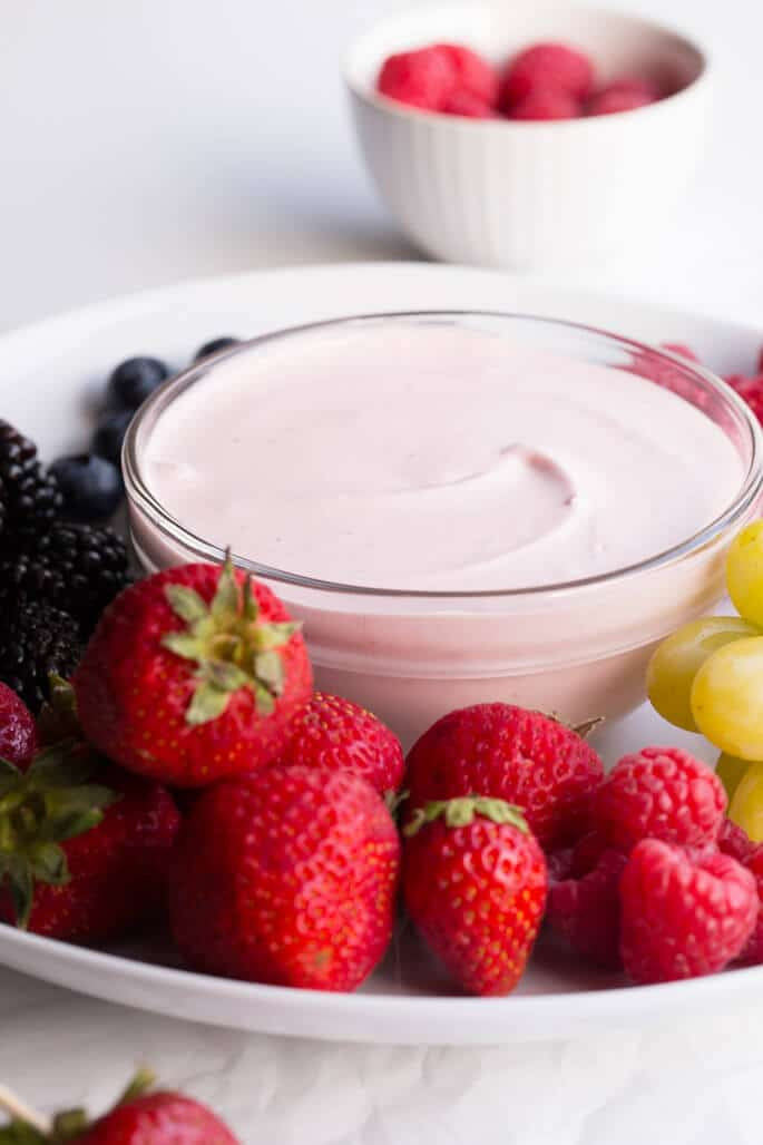 An assortment of fruit on a white plate with a bowl of strawberry fruit dip