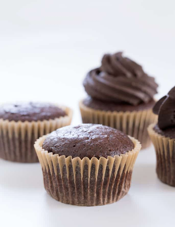 A close up of 4 chocolate cupcakes on a white surface