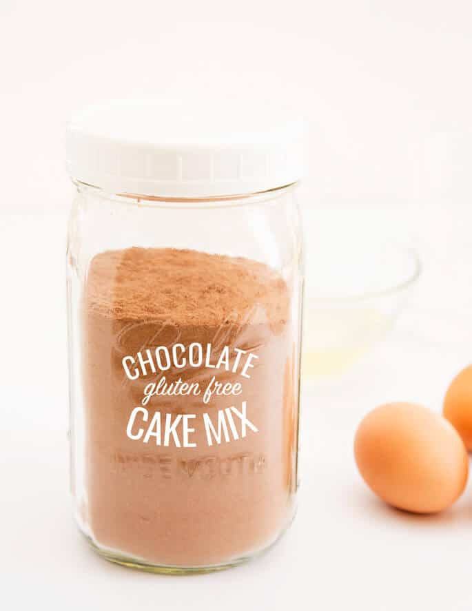 Chocolate cake mix in a jar with 2 eggs in back on white surface